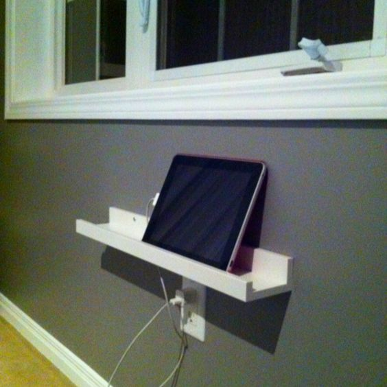 Use an IKEA picture ledge to display, store and charge iPad and iPhone. Simply drilled a hole in the bottom the picture ledge to put charger through!