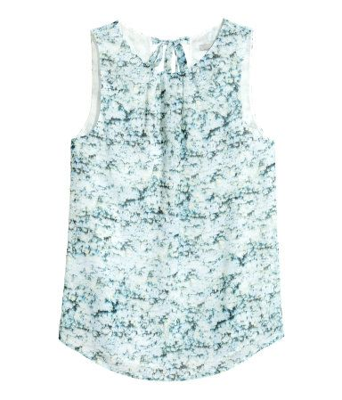 White/patterned. Sleeveless blouse in textured woven fabric. Decorative gathers at neckline, V-neck at back with horizontal strap, and tie at back of neck.