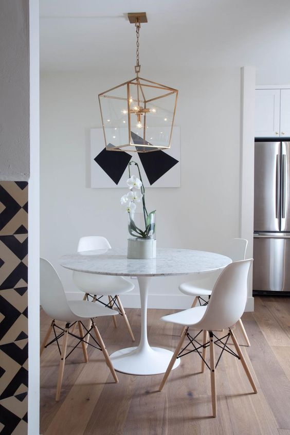 White Eames-style dining chairs surround the contemporary round dining table in this minimalist dining room. Wide plank European oak wood flooring ground the space, while a chic chandelier and abstract art bring in a modern note.: