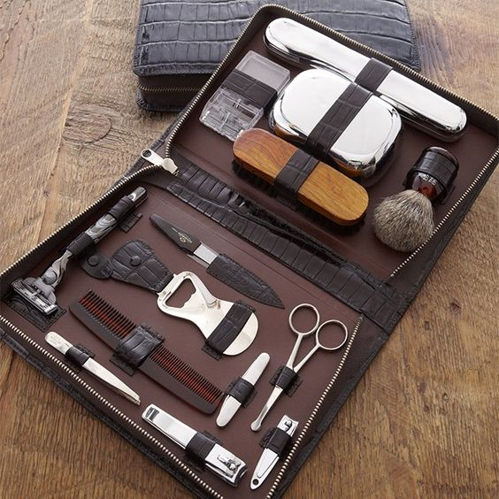 """Toiletry Kit -- This deluxe toiletry kit is the perfect travel companion for the well-organized man. Crocodile-embossed leather kit includes chrome soap dish, toothbrush, clippers, razor, shaving brush, and more; 8""""W x 2""""L x 11""""T. Made in Germany."""