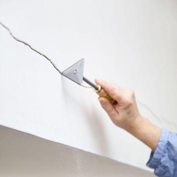 Étape 1 pour reboucher une fissure : utiliser un grattoir triangulaire pour bien nettoyer la fissure éliminer les résidus de plâtre