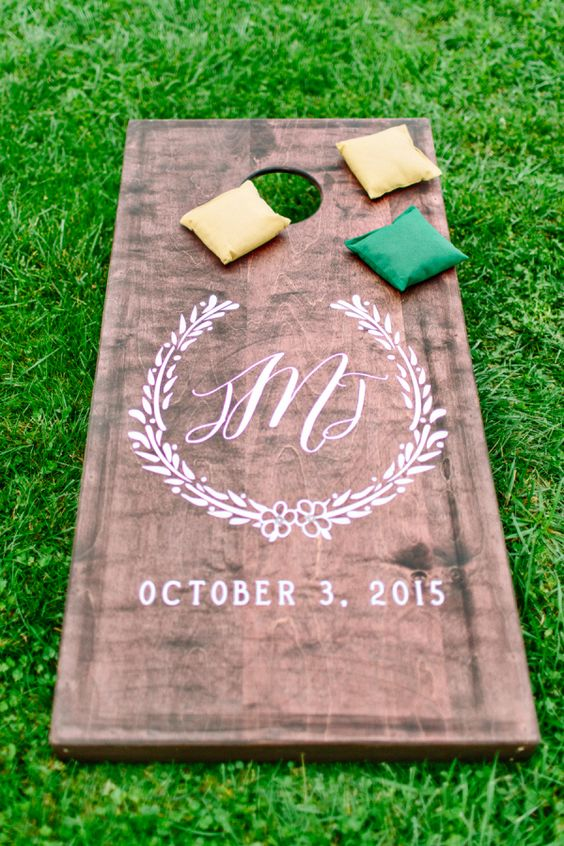 Fun and beautiful wooden engraved corn hole: http://www.stylemepretty.com/rhode-island-weddings/little-compton/2016/08/24/colorful-boho-bride-stunning-reem-acra-dress/ Photography: Kelly Dillon - http://kellydillonphoto.com/