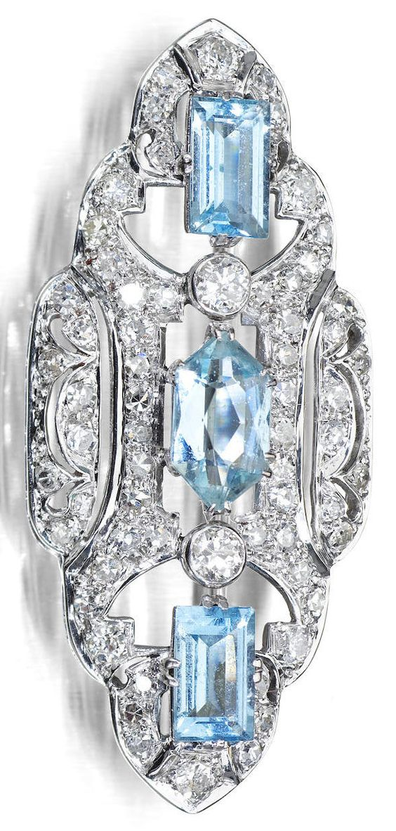 An Edwardian aquamarine and diamond brooch, early 20th century. Of scalloped lozenge-shape, set to the centre with a lozenge-shape aquamarine with a baguette-cut aquamarine to either side spaced by a pair of old round brilliant-cut diamonds, all surrounded by a pierced frame set throughout with old round brilliant-cut diamonds and single-cut diamonds, width 45mm. #Edwardian #brooch