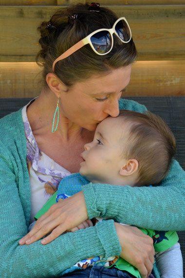 Mutter küsst Kind herzlich auf die Stirn, achtsame Haltung