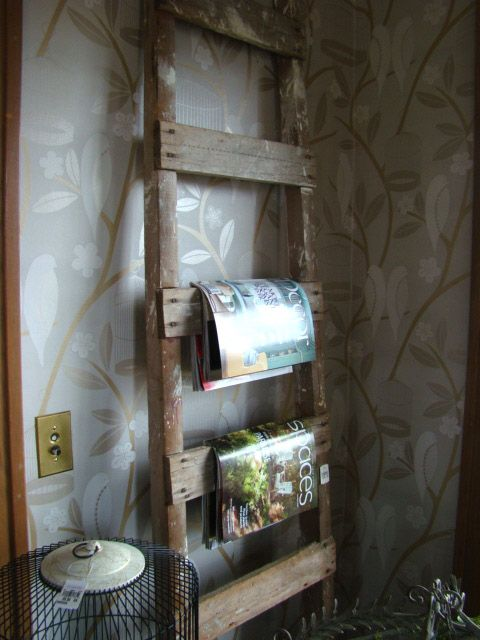 old ladder used as a hanging rack for magazines, towels or ...