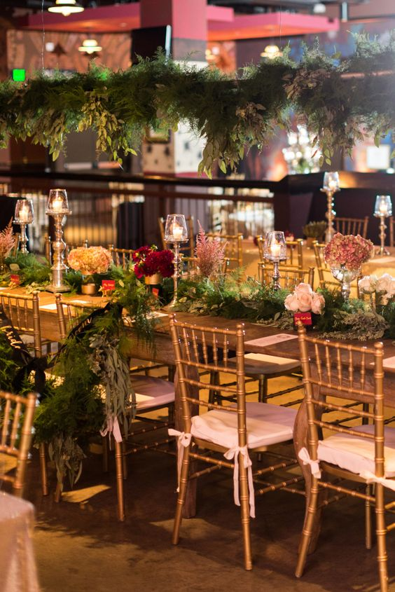 Midsummers Night's Dream-inspired head table with flower-filled vases, greenery, candles, and glittered fruits