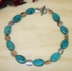 Cool rushing water of a mountain stream is the essence of this necklace, with wavy turquoise ovals and large silverplated discs. This necklace from Susen Foster secures with a silverplated toggle clasp.