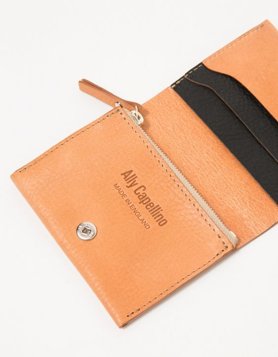 From Ally Capellino, a minimalist fold-over leather wallet in Tan.  Features crushed leather, snap button closure, three card holder, black leather interior, zipper pocket and pressed interior logo.  •Fold-over leather wallet in Tan •Crushed leather
