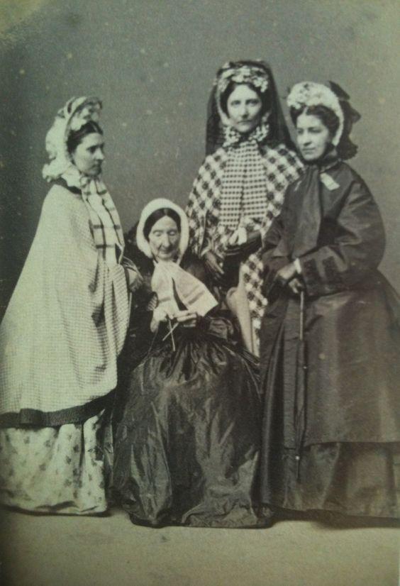 A group of 1860s ladies. American. Print dress, plaid shawl, knitting