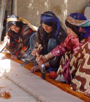 Drei Frauen in ihren traditionellen Gewändern knüpfen einen großen Teppich per Hand.