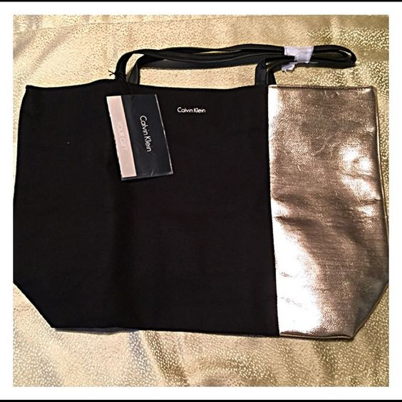 """NEW in Bag! Calvin KleinTote Huge..!! CALVIN KLEIN TOTE  20"""" wide 13"""" tall 5 1/2"""" base  NEW, but I see a scratch when in certain lighting..tried my best to photograph it..that's the best I can do. NEW IN BAG!!  NEW WITH TAG!! Gold & Black 9"""" handle drop..that's really great!!  Lasr photo pictures how it will be shipped to you..folded, as it was packaged during manufacturing.  Thank you,  Tazzygurl Calvin Klein Bags Totes"""