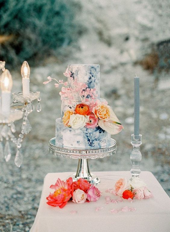 Blue and white marbled, textured cake complimented by orange and peach flowers make this cake ultra dreamy. Bring beachy tones indoors with this beauty.