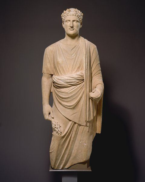 Greek. The Man Is Wearing A Doric Chiton With A Himation Draped Over It. He Has What Appears To