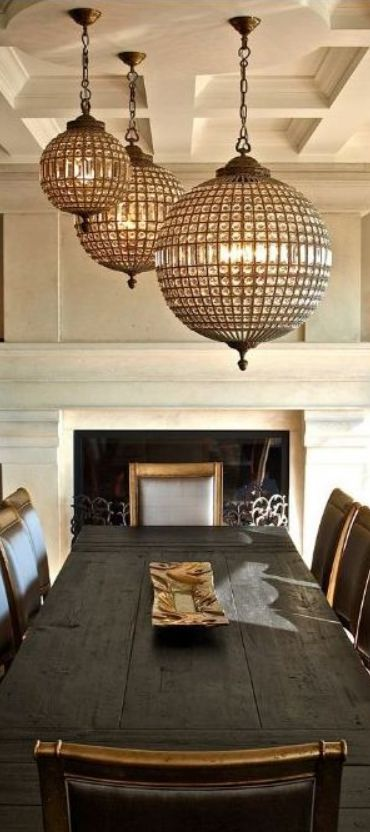 Triple threat these orb shaped crystal chandeliers hang above a rustic wood dining table w - Dining room chandeliers traditional ...