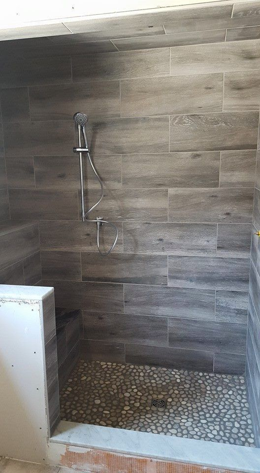 cool wood grain porcelain shower and river rocks! (stephen belyea