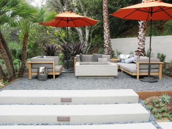 terrasse gravillonnée aménagée avec un salon de jardin en bois et des parasols