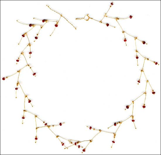 "18k gold branches with rubies and 19th century gold-plated glass beads. 15"" long."