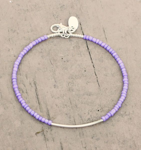 "$7.00 - This dainty bracelet is made with lilac seed beads and silver plated findings with an oval charm.  It measures 7.5""."