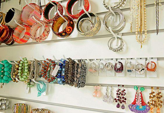Presos a uma régua de madeira, os puxadores de porcelana e o de ferro em forma de borboleta deixam os colares organizados e à mão