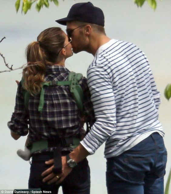 Gisele Bundchen steals a kiss and pat on the bottom from Tom Brady before swinging from a tree at the park