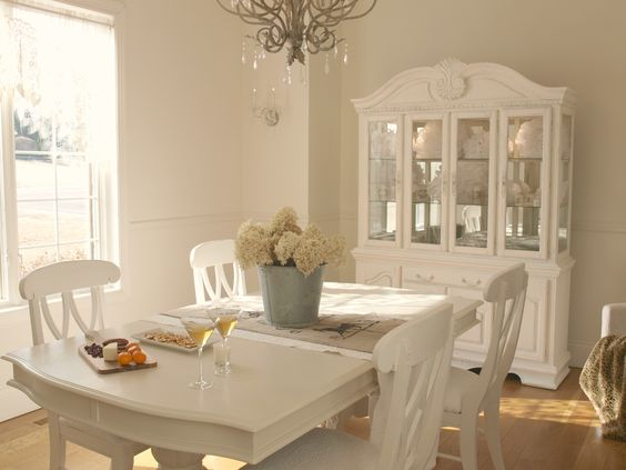 Timeless and tranquil feminine romantic dining room with shabby chic style/white dining buffet and hutch/white painted table and chairs/galvanized vase/hydrangea/antiqued silver chandelier/white oak hardwood flooring/Hello Lovely Studio