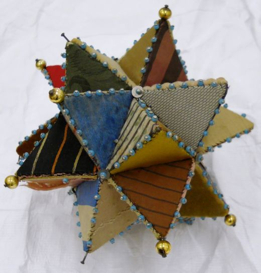 Victorian Patchwork Star Pincushion ca. 1880 -1910.  Decorative Victorian star shaped pin cushion, consisting of 60 individual silk and velvet covered triangular card templates that create a three dimensional star.  Photo credit:  The Quilt Museum and Gallery, which is an independent museum operated by The Quilters' Guild of the British Isles.