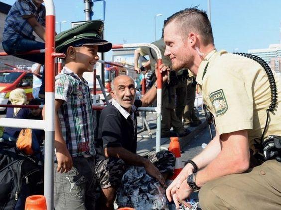 Un poliziotto di monaco gioca con un bambino appena arrivato in Germania
