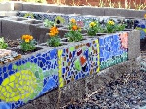 Cinderblock raised garden bed decorated with mosaic designs in vegetable and herb gardening