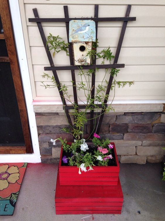 Spray painted crates turned into planters. Stained lattice. Add some flowers and a climbing plant for a quick and easy way to spruce up your front porch/patio.