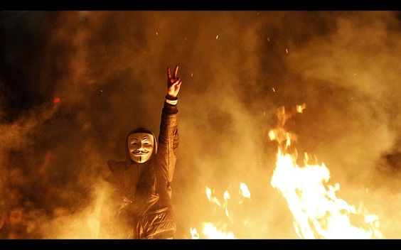 An anti-government protester wearing a Guy Fawkes mask gestures behind a barricade that they set on fire during a demonstration in Ankara, Turkey. Riot police clashed with demonstrators in several Turkish cities for a second day on Wednesday as mourners buried a teenager wounded in protests last summer, unrest which a defiant Prime Minister Tayyip Erdogan cast as a plot against the state.