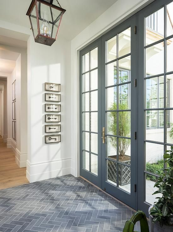 Gray slate herringbone tiles lead to a a gray glass paned front door illuminated by a bronze carriage lantern while framed vintage keys in shadow boxes are mounted the white wall of this stunning gray and white foyer.