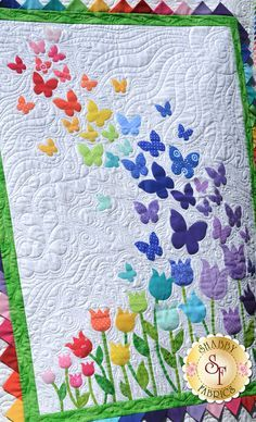 "Brighten your little girls room with this darling Blooming Butterflies Quilt! This Shabby Fabrics Exclusive quilt features a beautiful array of butterflies floating on a gentle breeze over a bed of blooming tulips, finished with bright prairie points for the inner border. Finishes to 40½"" x 51½""."