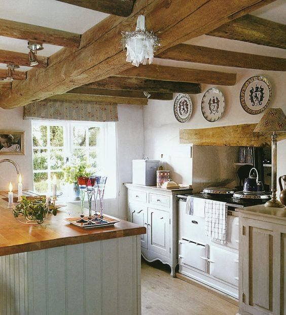Beautiful European country kitchen with rustic wood beamed ceiling and plates hung on wall. #kitchen #europeancountry #rustic #smallkitchen