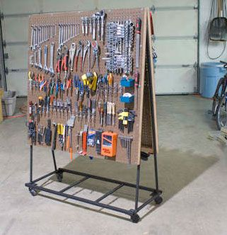 Garage: DIY rolling tool cart   Unclutterer. This would work great in a craft room also. Hooks for hanging bead strings. Peg board baskets for items. Repurpose soup cans for marker or brush holders. #StorageMart #OrganizeIt