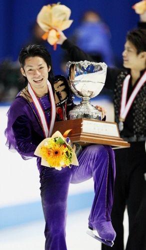 優勝し笑顔でトロフィーを掲げる高橋大輔(左)。右は2位の小塚崇彦=なみはやドームで2007年12月27日、貝塚太一撮影