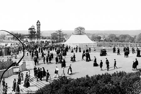 A view of Alexandra Park on a busy Bank Holiday with crowds of people. The Palace was built as a rival to Crystal Palace but was never as popular.