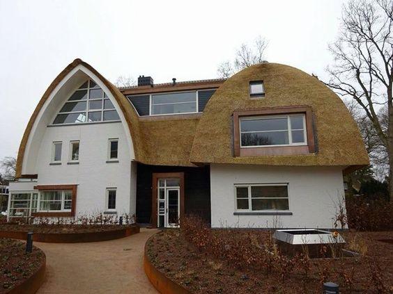 Witte villa met halfronde rieten dak. Koperen dakkapellen en accenten