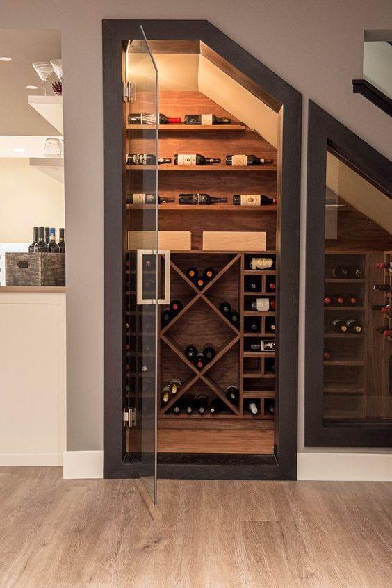 Cave à vin aménagée sous un escalier avec porte vitrée