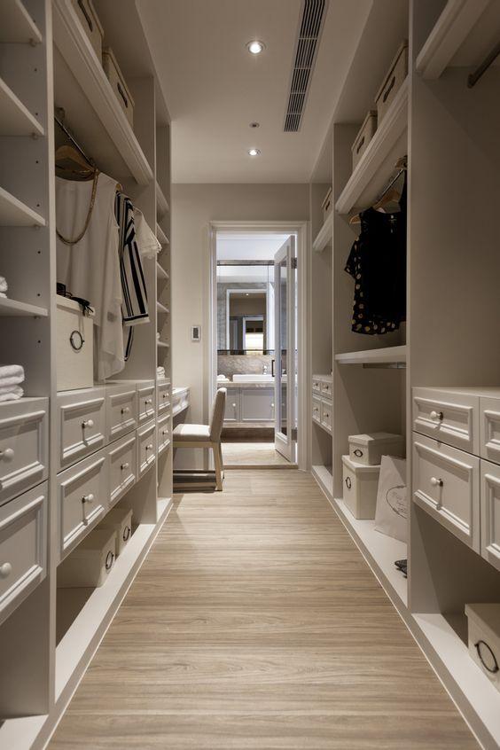Walk-in closet with white cabinets and wooden flooring #white #closet #storage #organization #allenrothCloset #allenAndRothCloset #closetShelves