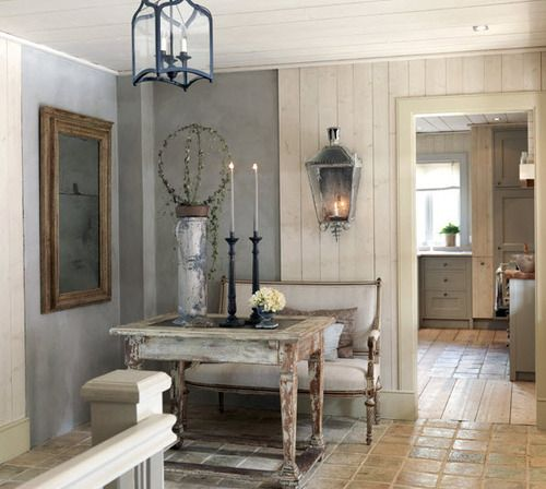 """look of """"concrete aged"""" sheet rock, flanked by vertical planks...Lantern sconce is to scale because it is balanced by painting...love the composition of this room"""