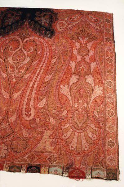 Umschlagtuch mit indischem Muster (französisches Tuch). Rechteckige Tuch mit vom schwarzen Mittelstück ausgehenden Gesamtornament ist später zusammengenäht worden. Von 4passähnlichen Mittelmotiv gehen in schwungvollen Linien Ranken-, Palmetten- und abstrakte Motive aus. Grundfarben sind Rot, Gelb, Grün und Schwarz. Tuch hat stilisierte Bordüre, und an Enden befinden sich merkwürdig abgeschnitten wirkende Muster in kräftigeren Farben. Es ist aus Hadersleben. Jarplund-Weding 1850-1900…