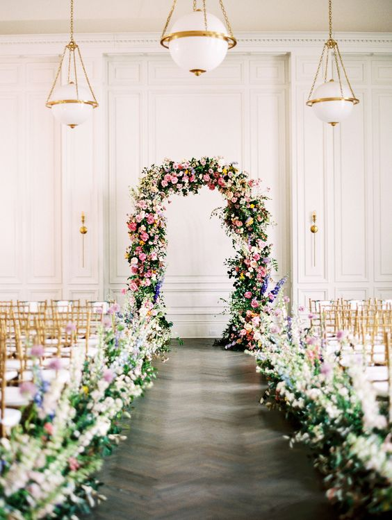 This couple who is high school sweethearts, brought a lot of love into this indoor garden wedding theme. Using pastel colors and tons of flowers the day was truly beautiful! This large floral arch was a great centerpiece at the ceremony! #Wedding #Flowers #Ideas #Garden #Purple #Yellow #Pink #Blue #WeddingDetails #Inspiration | Martha Stewart Weddings - These High School Sweethearts Created an Indoor Garden at Their Texas Wedding