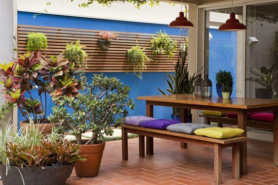 Na parede azul, os vasos estão pendurados no ripado de madeira. Projeto de paisagismo assinado por Gil Fialho com arquitetura de  Bernardes + Jacobsen