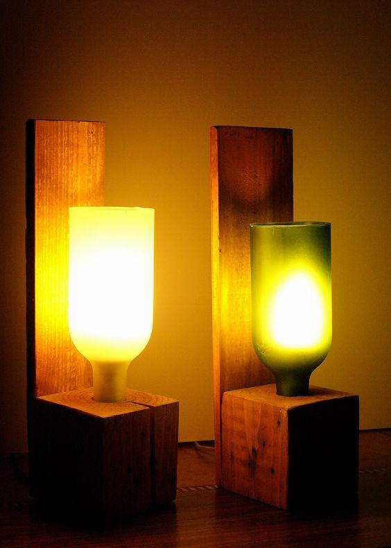 Lâmpadas com garrafas recicladas junto com uma paleta de madeira como suporte.:
