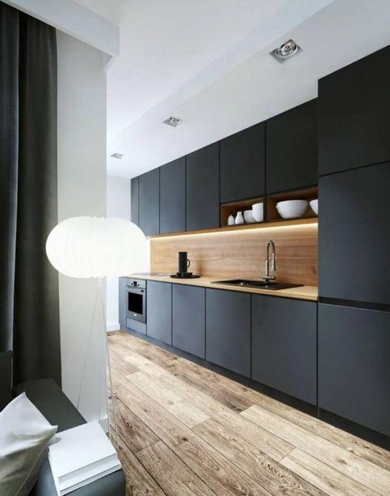 Une cuisine noire mat avec plan de travail en bois clair et un superbe plancher massif.