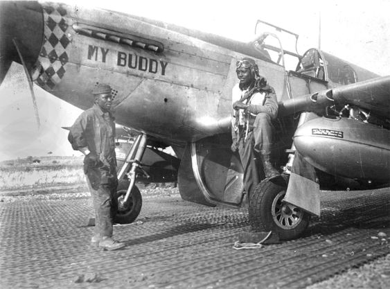 Lt. Charles Bailey in his flying gear with his boot on the wheel of the P-51 Mustang named for his father. He shot down a German fighter flying this plane while serving in the all-black 99th Fighter Squadron in Europe during World War II.