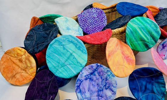 A bunch of circles in different batiks individually quilted then sewn together to hang on the wall.  I wanted to have the look of a cathedral window pattern. An interesting art quilt.