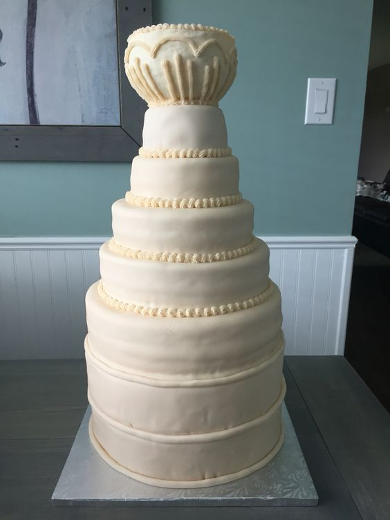 Stanley Cup Wedding Cake - White chocolate cake with Irish cream buttercream filling, cream coloured fondant with white chocolate cup on top