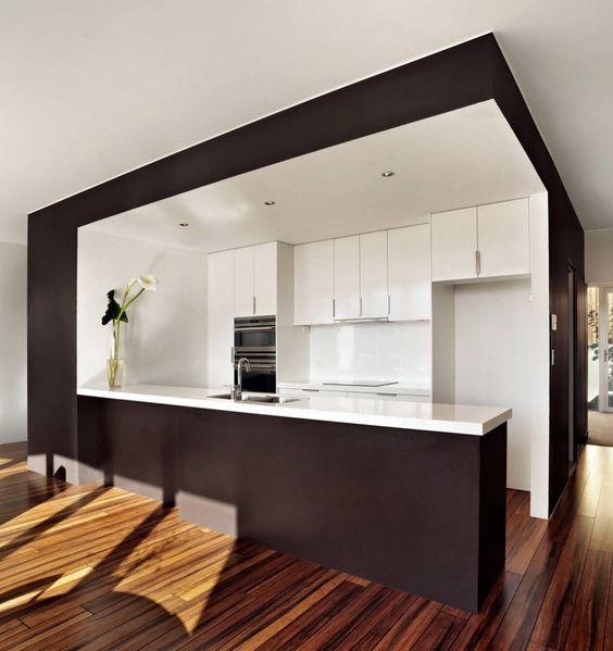 cocina abierta con barra americana, muebles y encimera de color blanco, suelo de parquet