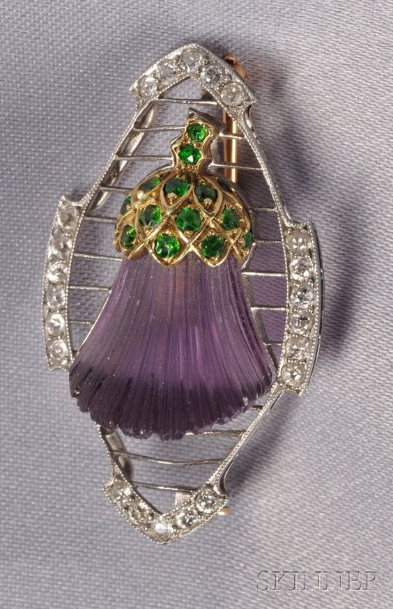 Art Deco Platinum, Amethyst, and Demantoid Garnet Thistle Brooch, the carved amethyst thistle with 18kt gold and demantoid garnet melee cap, resting on knife-edge bars, old mine-cut diamond melee edges, lg. 1 1/2 in. [This is really strange. I wonder if it was made for some specific purpose or organization]: